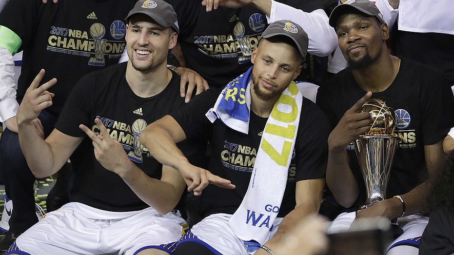 (From left) Golden State Warriors guard Klay Thompson, guard Stephen Curry and forward Kevin Durant celebrate after winning Game 5 of basketball's NBA Finals against the Cleveland Cavaliers in Oakland, California, June 12, 2017. The Warriors beat the Cavaliers 129-120 to take the NBA championship. Photo by: AP Photo/Marcio Jose Sanchez