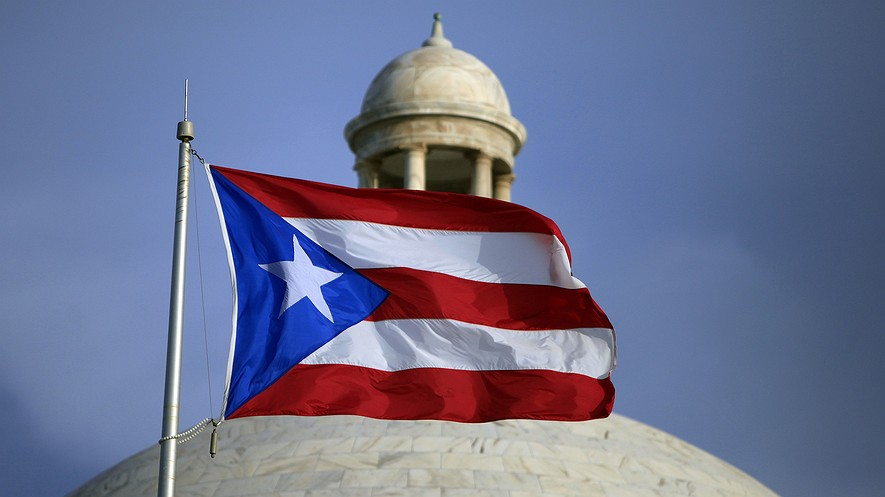 Puerto Rico's flag flies in front of its Capitol in San Juan. The governor announced that the U.S. territory overwhelmingly chose statehood on June 11, 2017, in a non-binding referendum held amid a deep economic crisis that has sparked an exodus of people to the U.S. mainland. Voter turnout was just 23 percent. Photo by: AP Photo/Ricardo Arduengo