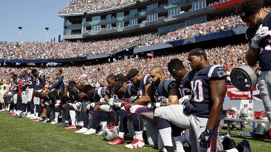 Several New England Patriots players kneel during the national anthem before an NFL football game against the Houston Texans, September 24, 2017, in Foxborough, Massachusetts. Photo by: AP Photo/Michael Dwyer